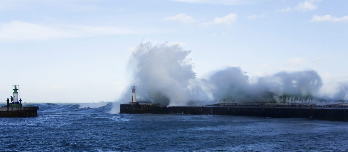 Waves crashing over lighthouse in Kalk Bay Harbour as fishermen brave storm, Cape Town, South Africa.