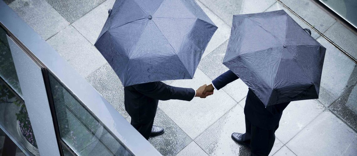 Businessman_shaking_hands_in_rain