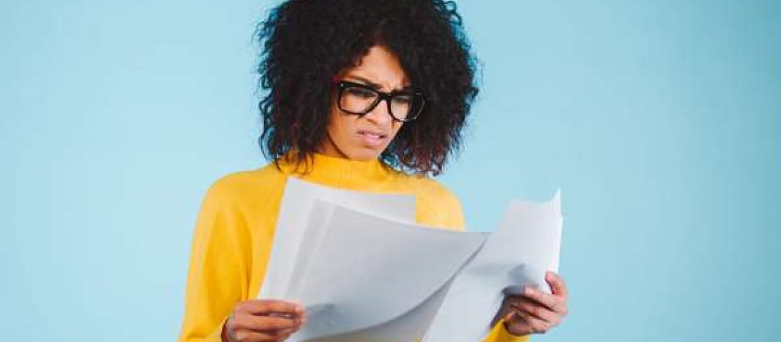 Businesswoman confused looking at documents