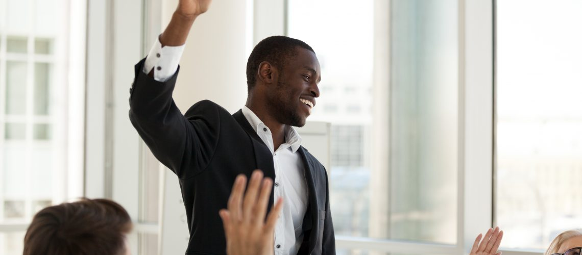 Black male mentor hold teambuilding meeting with diverse colleagues, mixed employees involved in training activity raise hands at office briefing, African American coach interact with workers