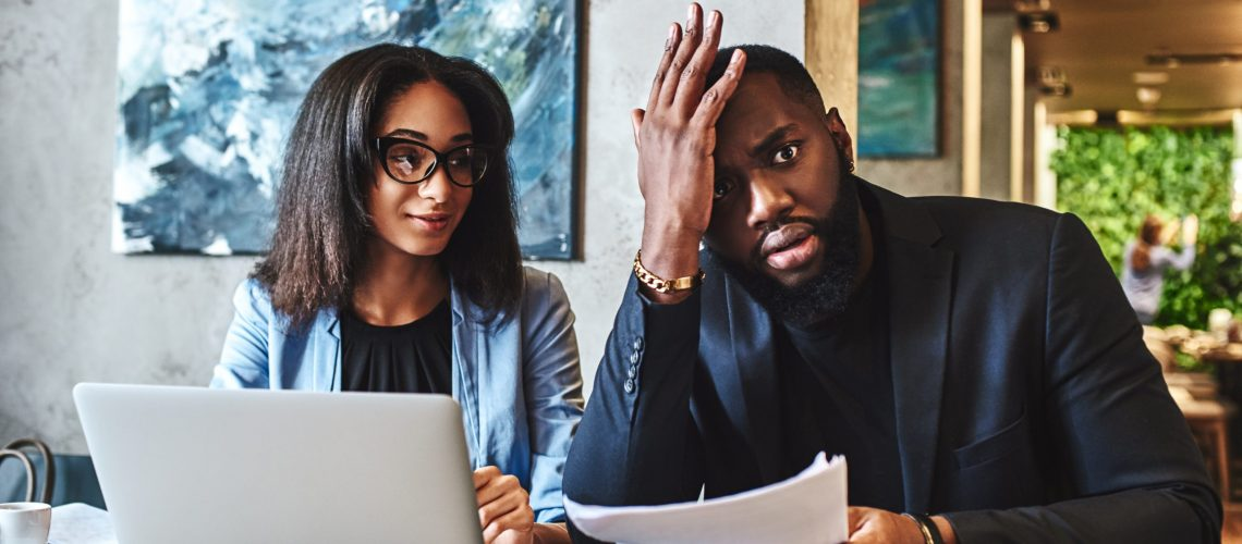 African american businessman and businesswoman are having lunch at restaurant, sitting at table near window, drinking coffee, discussing project, looking through working papers. Man is tired, holding hand on his head, while woman is looking at him with a smile