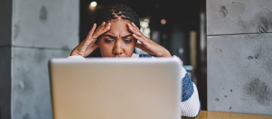 Confused female freelancer reading new task from work during distance job with laptop device in coworking space, unhappy woman have problem with payment via modern netbook feeling headache indoors