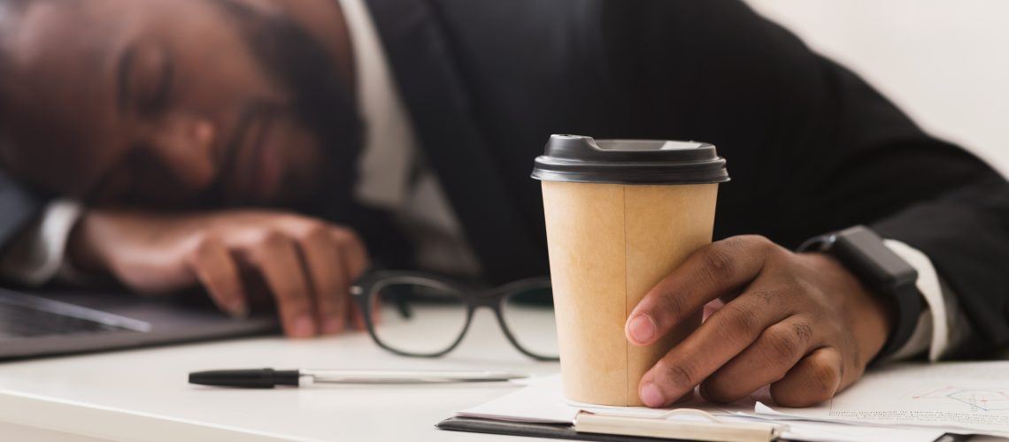 Exhausted african business clerk holding cup of coffee and sleeping at workplace, burnout concept