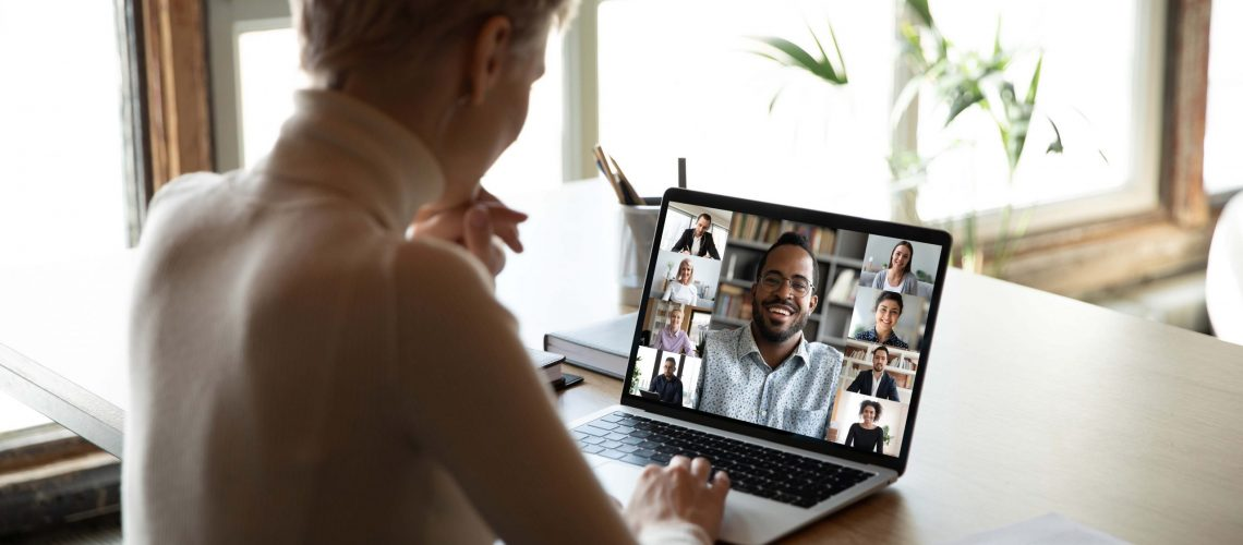 Woman sitting at workplace desk taking part at group on-line meeting using webcam laptop and videoconferencing app, view over female shoulder. Modern tech, distant webinar, online negotiations concept