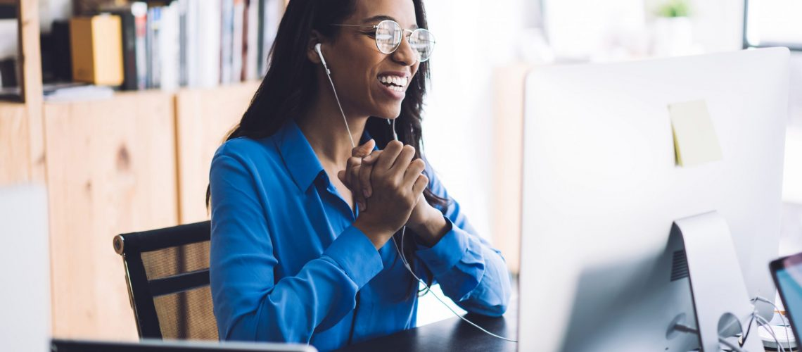 Happy young African American female office worker in blue shirt and glasses sitting at work table with  hands together wearing headphone and conducting online negotiations with coworkers