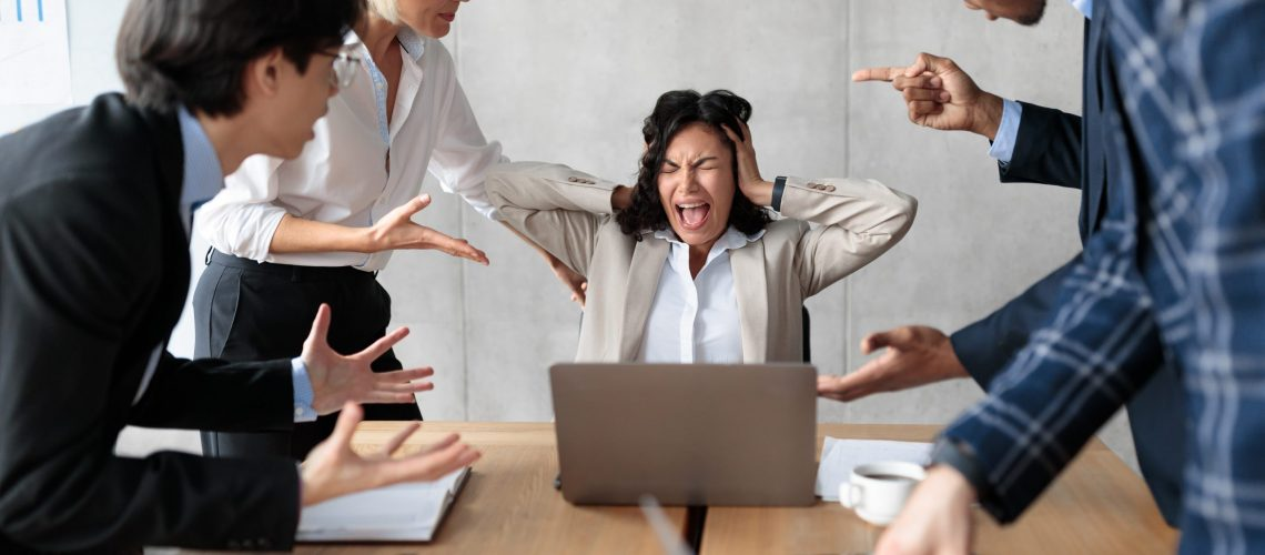 Conflict At Work. Unhappy Businesswoman Screaming Covering Ears While Aggressive Coworkers Shouting At Her Sitting In Modern Office. Corporate Communication Problem, Adult Bullying And Blaming