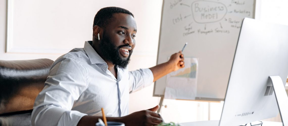 Handsome confident influential african american business coach with beard conducts online training for colleagues or students sitting at table and pointing at flipchart while look at computer screen