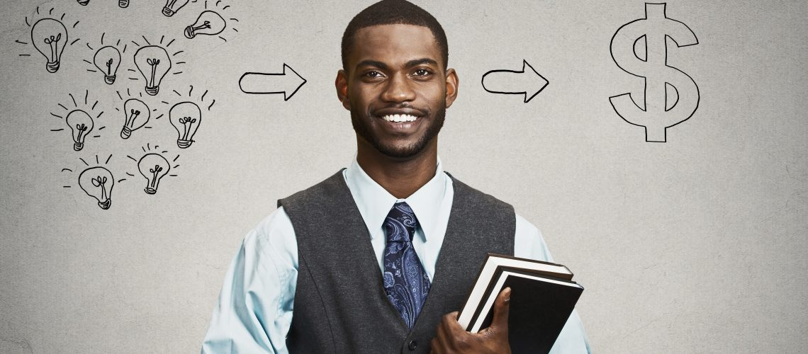 Happy, smiling handsome man holding books has ideas ready for financial success isolated black grey wall background. Positive human facial expression dynamism. Education economics concept