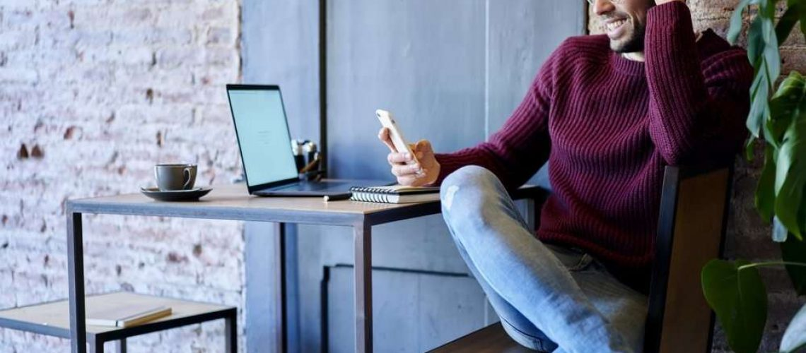 Happy businessman smiling at phone