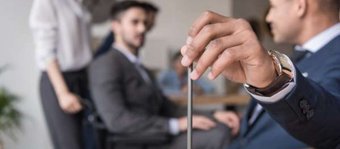 businessman holding pencil in meeting